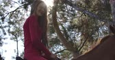 saddle : Caucasian female equestrian in pink clothes sitting in sunlight on brown horseback in autumn forest. Young woman resting with graceful animal outdoors. Cinema 4k footage ProRes HQ.