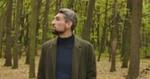 yaprak döken : Close-up of a handsome gray-haired Caucasian man with brown eyes standing in the forest and looking around. Guy in casual clothes enjoying calm quiet autumn day alone. Cinema 4k footage ProRes HQ. Stok Video