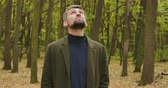 yaprak döken : Close-up of a gray-haired Caucasian man standing in the forest and looking up. Guy in casual clothes enjoying calm quiet autumn day alone. Cinema 4k footage ProRes HQ.