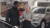 verkoopster : Confident African American man in black suit talking with female Caucasian car dealer in showroom. Blond woman holding tablet and explaining specifications to customer. Car dealership, car business.