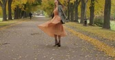 gęś : Charming Caucasian girl with long brown hair and grey eyes spinning in the autumn park. Elegant girl in mustard dress with crows feet print resting in the autumn park. Cinema 4k footage ProRes HQ. Wideo