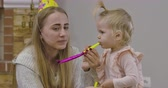 mladých dospělých : Close-up portrait of beautiful Caucasian woman and little cute girl playing with party whistles at home. Young mother in party hat admiring her adorable baby daughter. Cinema 4k footage ProRes HQ.