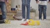 oynak : Legs of three children of different ages dressed in casual jeans jumping. Brothers and sisters having fun at home. Leisure, happiness, enjoyment. Stok Video