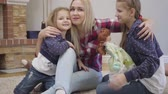 Portrait of happy Caucasian blond woman hugging and kissing daughters. Young mother taking care of her children indoors. Happiness, joy, leisure. Camera zooming in.