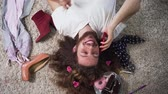 liberalism : Top view of happy Caucasian intersex person lying on soft carpet and talking on the phone. Portrait of binary gender man with makeup on face and flowers in curly hair surrounded with feminine stuff. Stock Footage