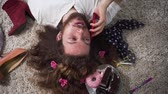 меньшинство : Camera moving around face of positive Caucasian intersex person talking and hanging up phone. Top view portrait of binary gender man with makeup on face and flowers in hair. Стоковые видеозаписи