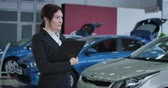 дилер : Portrait of Caucasian female car dealer standing in dealership with document holder and thinking. Serious businesswoman working in showroom. Auto industry, trading. Cinema 4k ProRes HQ.