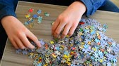 uczenie się : Teenager collects puzzles on coffee table. Wideo