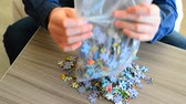 uczenie się : Teenager pours puzzles out of package on table.