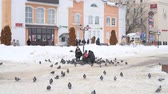 suíça : Dmitrov, Russia - March 10. 2018. family feeds pigeons on Sovetskaya Square Stock Footage