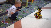 Belarus, Minsk, Robot Exhibition, June 3, 2019: boy playing child toy robot tractor man rides in the childrens room