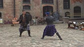 zwaarden : Belarus, the village of Mir, Mir Castle, June 16, 2019: theatrical look at the history of Belarus, a battle with the swords of two men of the Middle Ages, people from Scotland Stockvideo