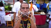 Thailand, Phuket, October 7, 2019: close-up portrait of Thai man of Chinese descent with pierced cheek pierced by a lot of metal knitting needles at the annual festival of Vegetarianism in Phuket Town