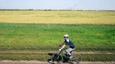 trial : AERIAL: Young man cycling on bicycle at rural road through green and yellow field. Stock Footage