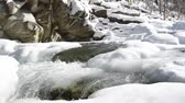 long exposure : a winter river with waterfall and icy shore, fast streams of melt water