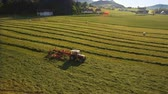 fieldwork : Aerial of Tractor collects Hay on the field in a green line sunny day in the mountains in 4K