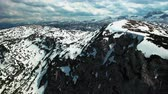 Aerial panoramic view of snowy mountains with rocks. In the background beautiful scenic nature