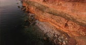 Aerial view of the precipice with terrible rocks by the sea at sunset Stock Footage