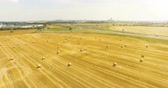 Aerial view of cropped wheat field with bales of hay in the countryside. View of the highway with driving cargo on a sunny day Stock Footage