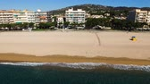 Aerial view of yellow sandy beach with people on the coast. Spain, Catalonia