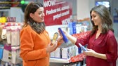 xampu : Customer choosing cosmetic products in supermarket talking to sales representative woman Vídeos