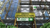 uithang bord : Building under construction with scaffolding and signboard.