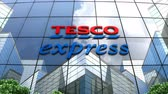 облака : August 2019, Editorial use only, 3D animation, Tesco Express convenience store logo on glass building. Стоковые видеозаписи