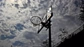 file : Outdoor basketball hoop low angle with clouds moving in time lapse