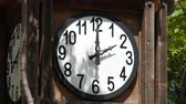 an : Steady shot of white round clock mounted in a wooden crate, without a second hand