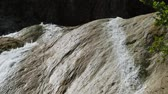 Wide shot of water cascading down a slippery rock at the top of a waterfall, with sounds