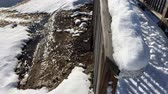 gleccser : Ice and snow melting on the ground and on the railing of a small wooden bridge