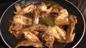 vařené : Hand-held shot of chicken wings frying in a pan, with sizzling sounds