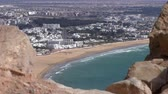 kasbah : New modern African Morocco seaside city Agadir beach view from top of the hill with blurred old ruined stone wall in foreground