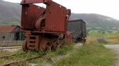 vintage : Abandoned rusty vintage mining machine on railroad track on the slope of the hill