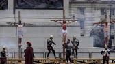 crucificação : LONDON, ENGLAND, UNITED KINGDOM - APRIL, 2017: Outdoor public reenactment performance showing Jesus Christ passion in the city square. Roman soldier is finishing hammering last nail into crucified Jesus feet Stock Footage