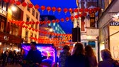 corner : LONDON, ENGLAND, UNITED KINGDOM - APRIL, 2017: Rickshaw driver sitting on seat of his brightly illuminated vehicle at night in Londons Chinatown, China Town, Wardour Street corner is looking around for passengers Stock Footage