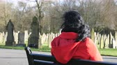 tomb : Rear view of lone sad dark long hair woman in red coat is sitting on bench in an old English cemetery on a sunny windy day in autumn or winter