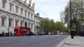 spojené království : LONDON, ENGLAND, UNITED KINGDOM - APRIL, 2017: Street scene in the heart of United Kingdoms City of Westminster, Central London, showing the Banqueting House, famous red double-decker buses and taxis on Whitehall
