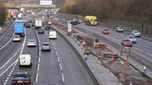 high speed camera : MANCHESTER, ENGLAND, UNITED KINGDOM - MARCH, 2018: Closer view of heavy traffic on a part of Manchester city ring road under reconstruction. M60 is upgrading into smart motorway Stock Footage