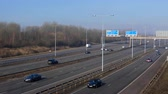 gantry : MANCHESTER, ENGLAND, UNITED KINGDOM - MARCH, 2018: High angle view of sunlit transport moving on multi-lane Manchester Ring Road M60 in the light morning haze; Muller milk dairy product truck driving by Stock Footage