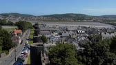 estuary : High angle view of old town Conwy in North Wales showing tourists walking on medieval wall of World Heritage Site, busy street, rooftops and river Stock Footage