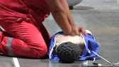 cpr : Woman in red uniform performing cardiopulmonary resuscitation, CPR on mannequin on the floor, side view Stock Footage
