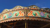 wesołe miasteczko : Colourful retro style carousel starting spinning; low angle view against blue sky
