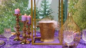 kuruluş : Purple and golden color colour dinner setting with burning candles and liquid nitrogen steaming from golden bucket for champagne Stok Video