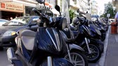 греческий : HERAKLION, CRETE ISLAND, GREECE - OCTOBER, 2014: Close up of row of motorcycles on a busy city centre center street Стоковые видеозаписи