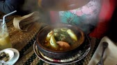 pincér : Moroccan cafe waiter brought fish tagine or tajine for a woman customer, then lifted cone shape lid. In the clay plate were vegetables and piece of fish in gravy; shaky table,handheld camera Stock mozgókép