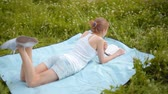 образование : Young Beautiful Slim Woman is Reading a Book Lying in the Park and Eating an Apple in Summer Стоковые видеозаписи