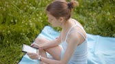 relaxation : Young Beautiful Woman is Reading the E-Book in the Park on a Blanket in Summer