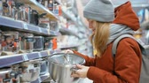 crock : Young Lady is Choosing a Crock Pot in the Houseware Department in the Shopping Center