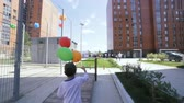 Mothers little son walking with colorful balloons after entertainment programme on the street between multi storey buildings infrastructure for healthy living and playgrounds place for children Stock Footage